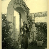 Woman in Fiesta costume standing in front of archway